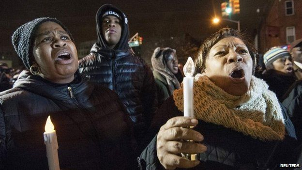 Prayers and songs at vigils for the officers shot dead in New York