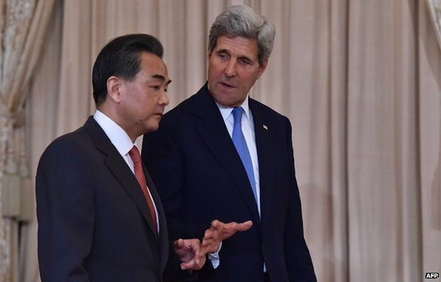 US Secretary of State John Kerry (R) speaks to Chinese Foreign Minister Wang Yi as they arrive to meet the press prior to talks in Washington, DC on 1 October 2014.