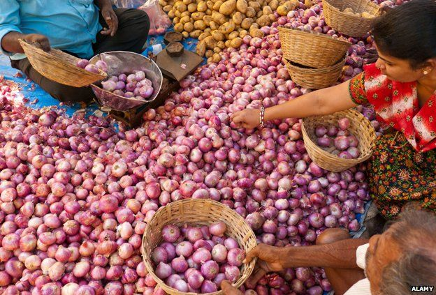 Customers buying onions at a market in India