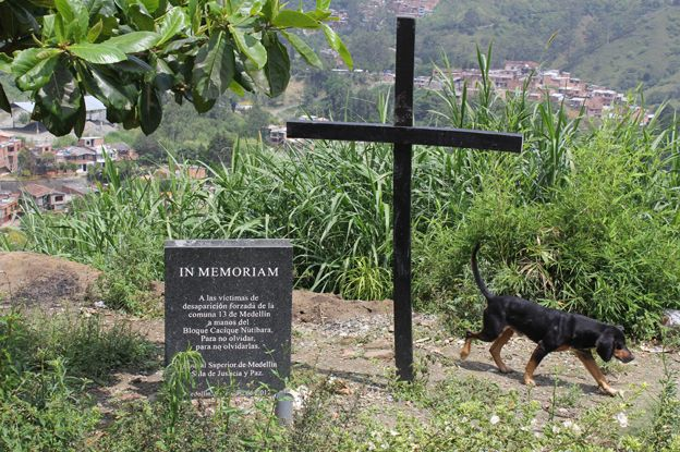A cross by a stone in memory of the disappeared