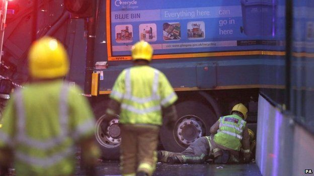 Firefighters looking under the lorry