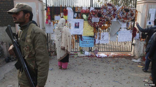 Soldier next to board for victims of Peshawar school attack