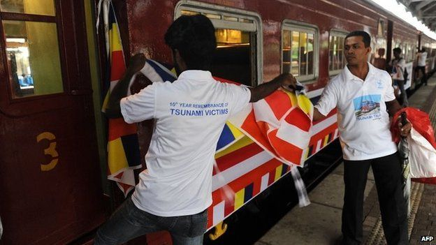 Sri Lankan railway employees place flags on a train compartment that was swept away during the 2004 tsunami and later retrieved and restored, as the Ocean Queen Express prepares to set off from the Colombo Fort railway station in Colombo on December 26, 2014