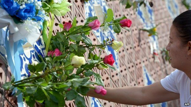 A Thai relative of a tsunami victim places roses on the Ban Nam Khem tsunami memorial park wall on the tenth anniversary of the 2004 tsunami in Phang-nga province on December 26, 2014