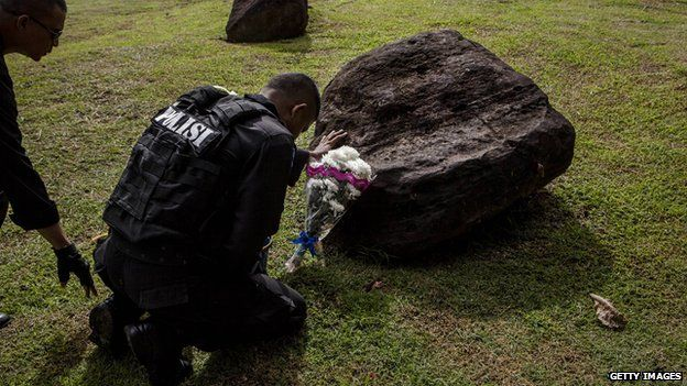 An Indonesian policeman prays at mass grave to commemorate the tenth anniversary of the Boxing Day tsunami on December 26, 2014 in Banda Aceh, Indonesia.