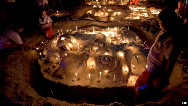 Thai students place candles on a sand sculpture during commemorations on the the tenth anniversary of the 2004 tsunami at Patong beach in Phuket province on December 26, 2014
