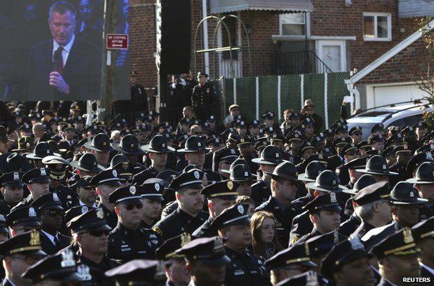 Officers turn their backs on Mayor Bill de Blasio outside the church in New York, 27 December