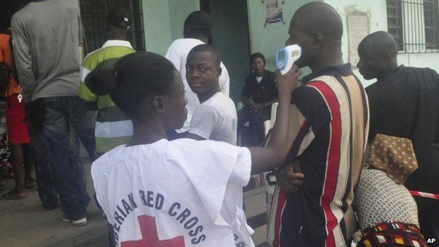 A Liberian red cross official takes the temperature of a man before casting his vote in senate elections
