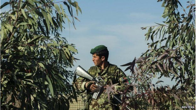 An Afghan National Army soldier stands amongst trees while guarding his post during a mission near forward operating base Gamberi in the Laghman province of Afghanistan on 28 December.