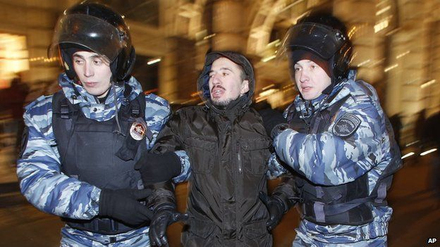 Police officers detain a protester during an unsanctioned protest in Moscow, Russia, Tuesday, Dec. 30, 2014