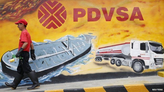 Worker pasts PDVSA mural in Caracas, Aug 2014