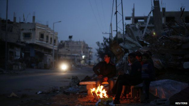 Palestinians warm themselves by a fire near the ruins of houses which witnesses said were destroyed by Israeli shelling during the most recent conflict between Israel and Hamas, in the east of Gaza City 1 December 2014.