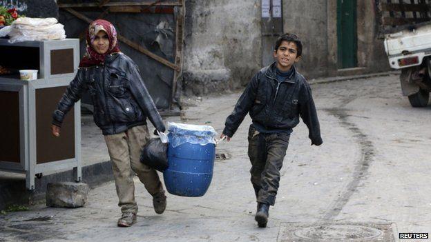 Children carry milk in Aleppo, Syria