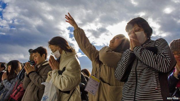 People pray and throw offerings for the new year at the Shinto Meiji Shrine in Tokyo (01 January 2015)