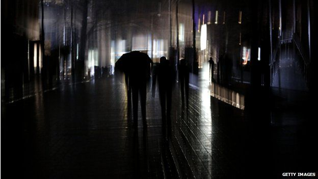A man walks with an umbrella during a power outage in the Crimean city of Simferopol