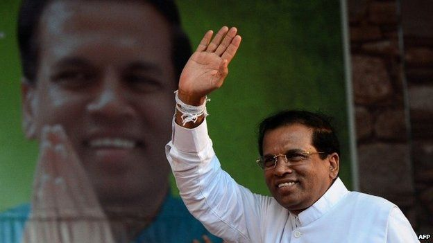 """This file photo taken on November 30, 2014 shows Sri Lanka""""s main opposition presidential candidate Maithripala Sirisena waving to the crowd during an election rally in the north-central town of Polonnaruwa."""