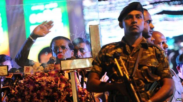 """Sri Lanka""""s main opposition presidential candidate Maithripala Sirisena (L) addresses his supporters from behind a bullet proof screen during an election rally in Colombo on January 5, 2015."""