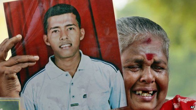 """In this Nov. 15, 2013 file photo, a Sri Lankan ethnic Tamil woman cries holding a portrait of her missing son during a protest demanding answers about the thousands who went missing near the worst war""""s end in 2009"""