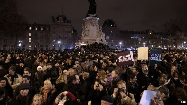 """People hold placards reading in French """"I am Charlie"""" during a gathering at the Place de la Republique (Republic square) in Paris, on 7 January 2015,"""