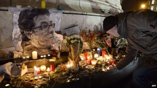 A man lights a candle next to a picture of late French cartoonist Tignous during a rally at Republic Square in Paris on 8 January 2015,