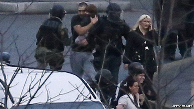 People, believed to have been hostages, were seen fleeing the supermarket with police