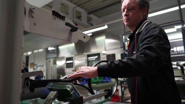 Head factory employee assesses a racquet