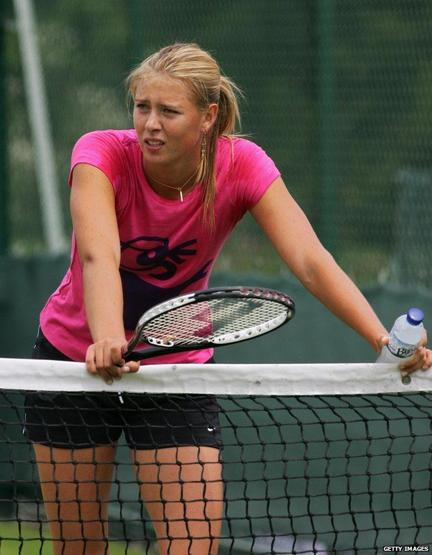 Maria Sharapova rests on a tennis net during training in London