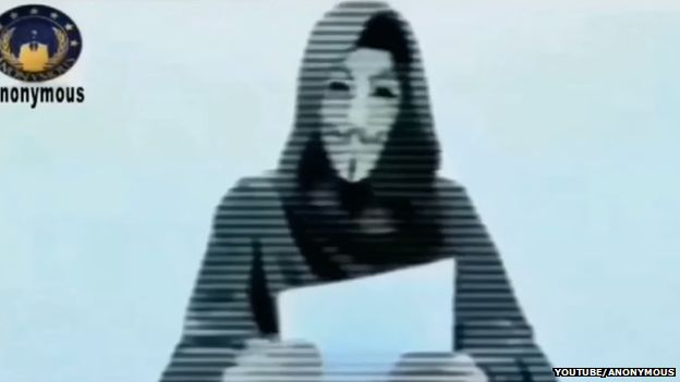A hooded and masked man reads out a statement