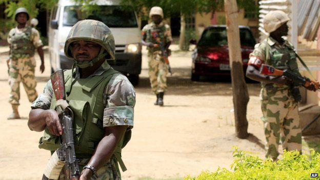 Nigerian soldiers stand guard at the offices of the state-run Nigerian Television Authority in Maiduguri (June 2013)