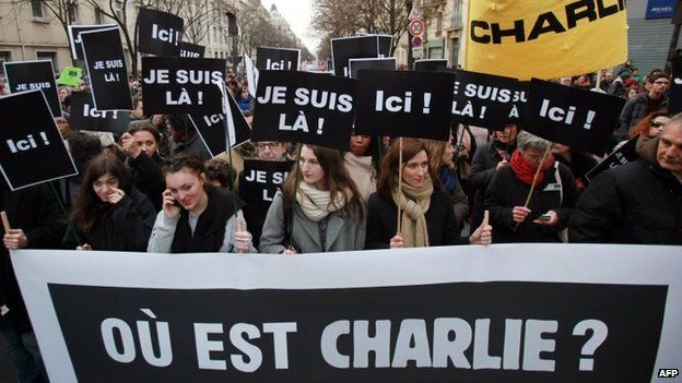 """People walk behind a banner reading """"Where is Charlie?"""" holding placards reading """"I am here"""" take part in a Unity rally Marche Republicaine at the Place de la Republique in Paris, 11 January 2015"""