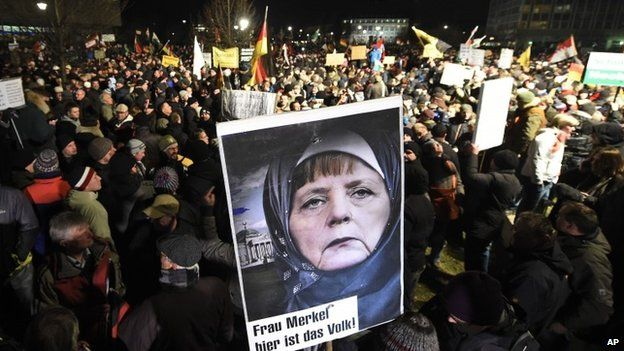 "A protestor holds a poster showing German Chancellor Angela Merkel wearing a head scarf in front of the Reichtstags building with a crescent on top and the writing ""Mrs Merkel here is the people"" during a rally of the group Patriotic Europeans against the Islamization of the West, or PEGIDA, in Dresden, Germany, Monday, Jan. 12, 2015."