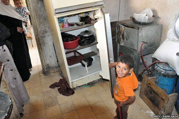 A young boy shows the inside of his family's fridge.