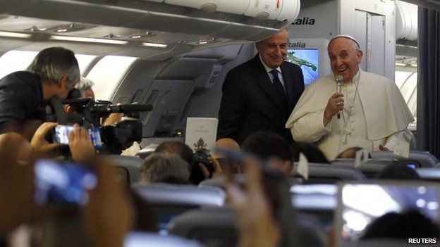 Pope Francis entertains reporters on an airplane