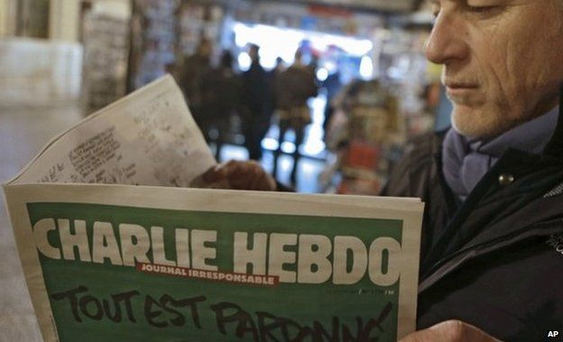 Jean Paul Bierlein reads the new Charlie Hebdo outside a newsstand in Nice, south-eastern France, 14 January 2015