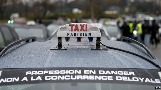 "A banner glued on a taxi that reads ""profession in danger, no to unfair competition"" during a taxi drivers demonstration in Paris, France, 15 December 2014"
