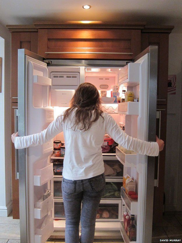 A woman in front of a well stocked fridge