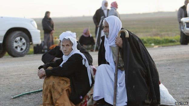 People from the minority Yazidi sect sit while waiting along a road on the outskirts of Kirkuk