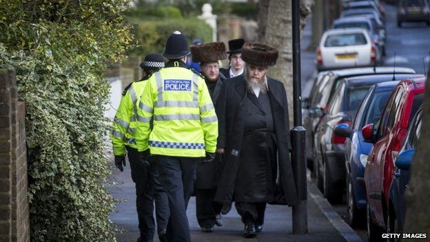 Police carry out a patrol as Jewish men walk past