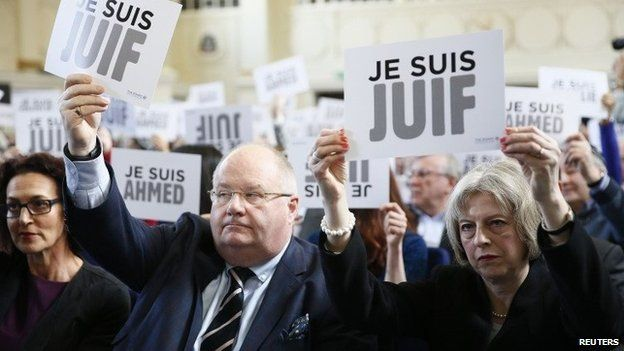 """Eric Pickles and Theresa May hold up signs reading """"I am Jewish"""""""