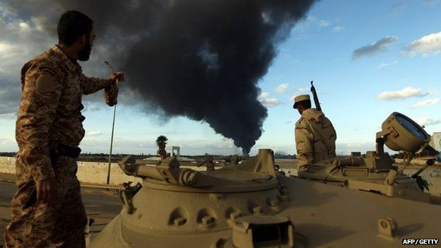 Members of the Libyan army stand on a tank as heavy black smoke rises after clashes against Islamist gunmen in the eastern Libyan city of Benghazi