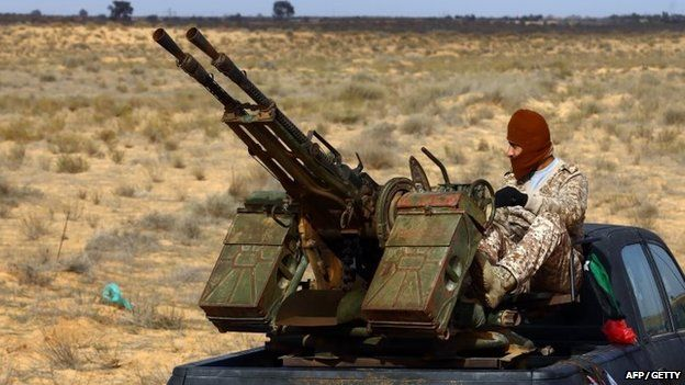 A fighter from the Fajr Libya (Libya Dawn) militia sits on a pick up truck mounted with a machine gun during clashes with forces loyal to Libya