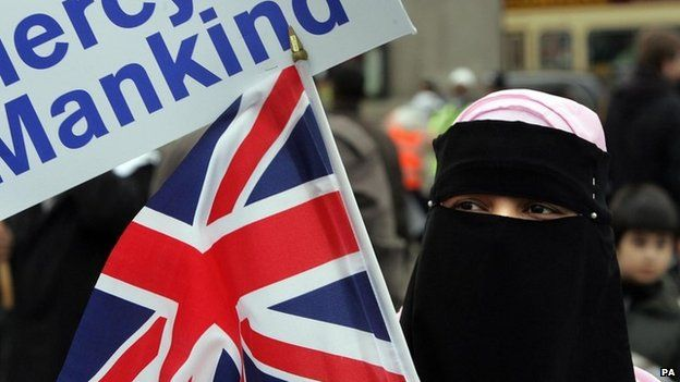A Muslim woman waves a British flag at a rally