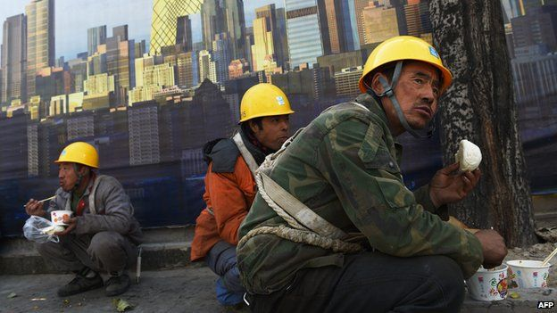 Workers eat lunch outside a construction site in Beijing