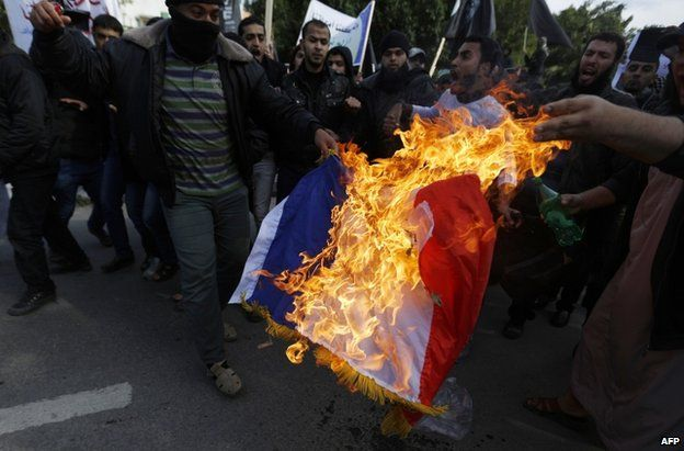 A Palestinian demonstrator burns a French flag in Gaza City, 19 January