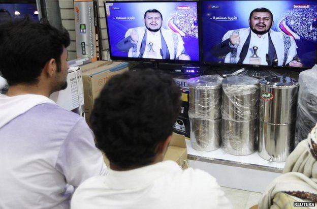 People watch as leader of Abdel Malek al-Houthi delivers a live speech in Sanaa, 20 January