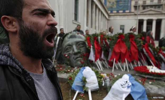 A supporter of the Greek Communist party shouts slogans in front of a monument inside the Athens Polytechnic school, on the eve of the 41st anniversary of a 1973 student uprising against the then military ruling junta in Athens, 16 November 2014.