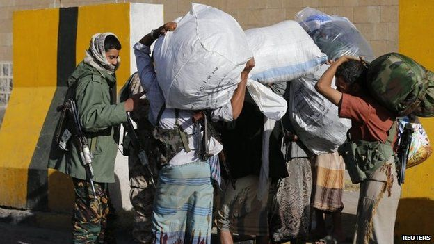 A Houthi fighter screens members of the Yemeni presidential guards - wearing civilian clothes - as they leave the presidential palace with their belongings in Sanaa (21 January 2015)