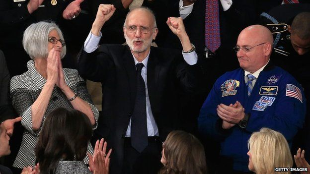 Alan Gross (C), recently freed after being held in Cuba since 2009, pumps his fist after being recognised by US President Barack Obama
