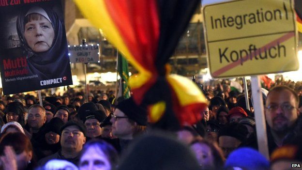 Participants of a Legida demonstration, a local offshoot of the Pegida in Leipzig, carry a placard depicting German Chancellor Angela Merkel wearing a headscarf