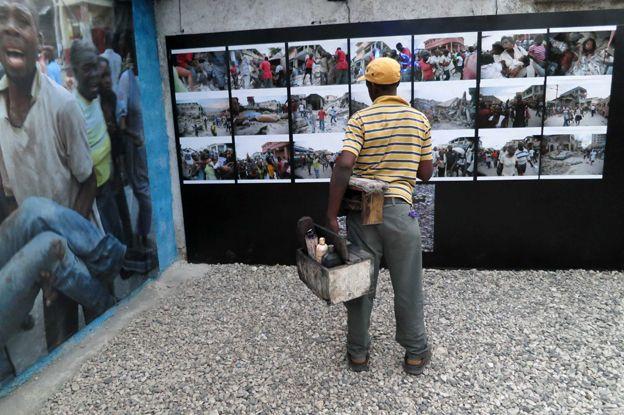 A shoeshine man looking at Morel's photos